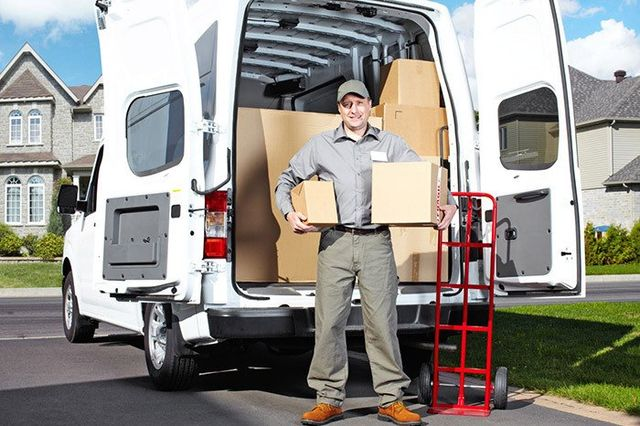 Transport moving man placing boxes in his van