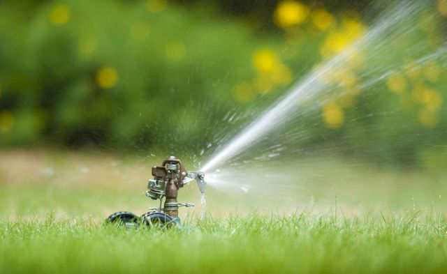 Water sprinklers on a lawn after pump installation in Lamesa, TX