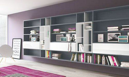 Una libreria di color grigio scuro con dei libri dentro, muri in color viola scuro e il tappeto di color viola