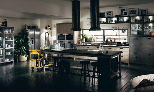 Una cucina arredata in colori bianco e nero, cornici sopra il buffet e un tavolo davanti la cucina con sedie del bar