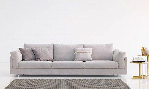 Un divano di color grigio a tre posti, un tappeto davanti e sulla destra dei tavolini in legno con dei oggetti