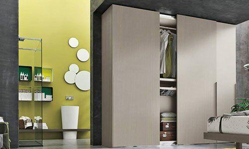 un armadio beige semi aperto e sulla sinistra una parete gialla con degli oggetti a forma circolare di color bianco appesi