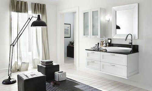 Un bagno con un mobile di color bianco con cassetti, lavabo e davanti un lampada da terra, due pouf di color nero e un tappeto