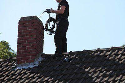 operaio su un tetto di una casa durante pulizia di una canna fumaria