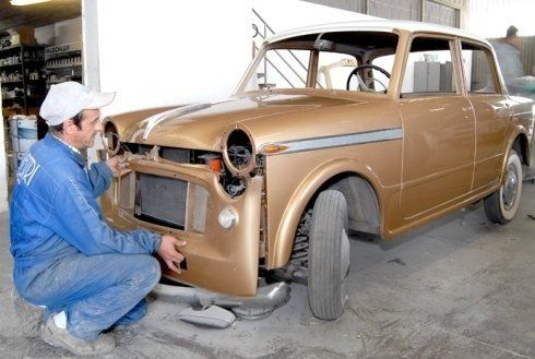 carrozziere che monta un ricambio originale su un'auto d'epoca