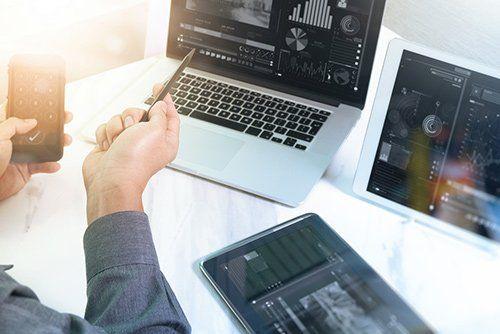 persona che consulta il cellulare tenendo una biro in mano di fronte a due computer portatili
