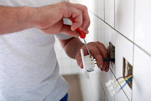 Elettricista mentre lavora su una spina con cacciavite alla una casa