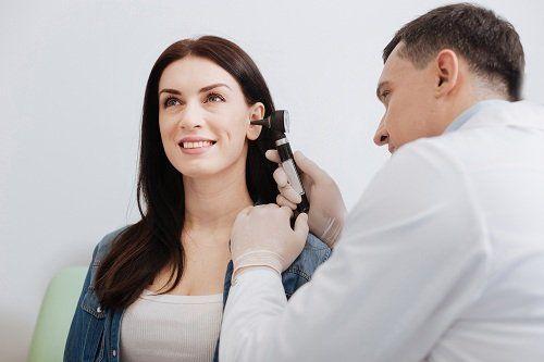 un medico che esamina un orecchio di una paziente