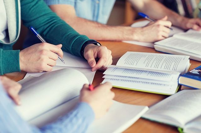 Close up of students hands with books or textbooks writing to notebooks