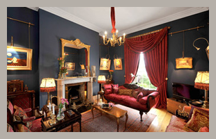 Living room with black walls and antique furniture