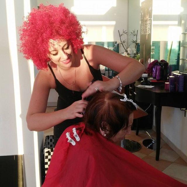 parrucchiera che applica tinta sui capelli di una cliente