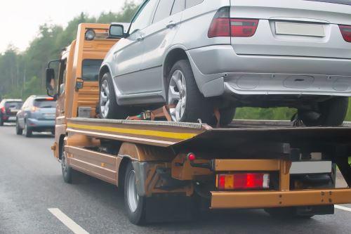 un carro attrezzi che trasporta una macchina su strada