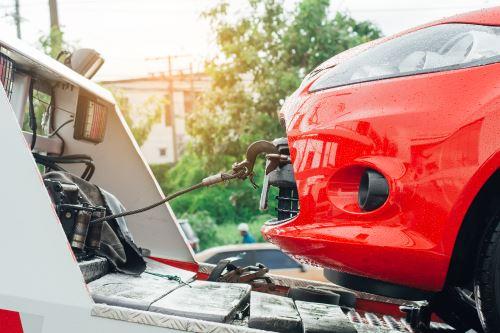 il gancio traino di un carro attrezzi agganciato a un'auto rossa