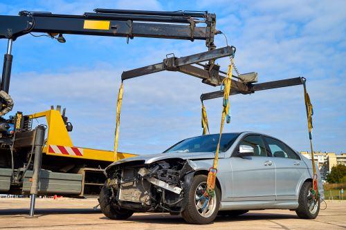 un carro-attrezzi e dietro una macchina pronta per essere caricata