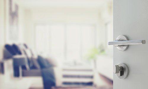 una porta di color bianco semi aperta e dietro l'immagine offuscata dell'interno dell'appartamento