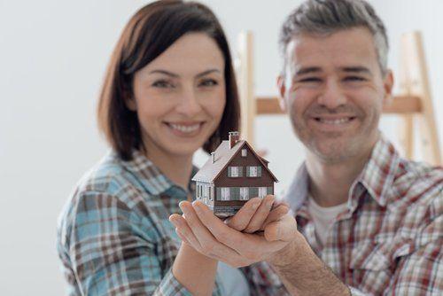 Una giovane coppia che sorregge una casetta di legno