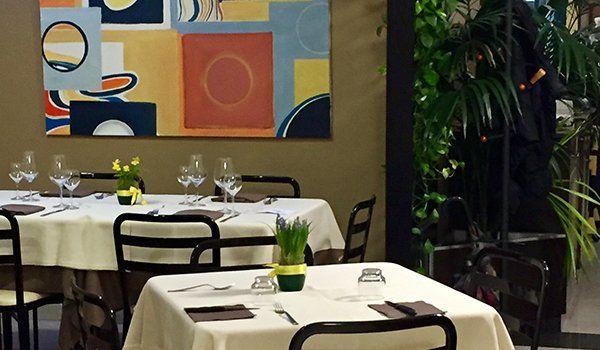 due tavoli apparecchiati e un quadro colorato appeso al muro all'interno del ristorante