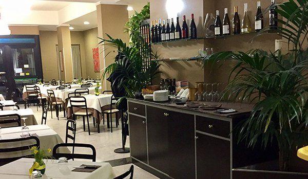 dei tavoli e sulla destra un mobiletto marrone con sopra dei bicchieri,dei piatti e sopra delle mensole con delle bottiglie di vino