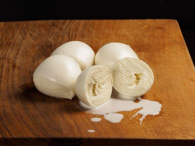 Delle mozzarelle di bufala su un tavolo, una è aperta a metà e perde copiosamente latte fresco
