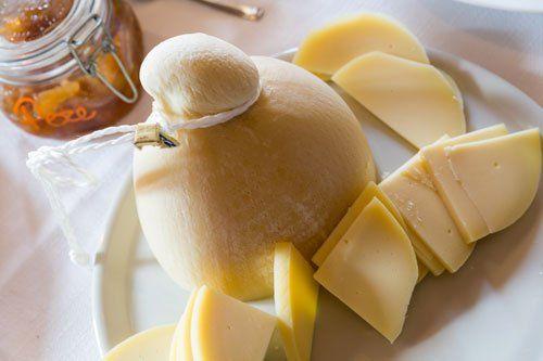 Una caciotta di scamorza affumicata e delle fettine di scamorza a fianco con un barattolo di composta di pere