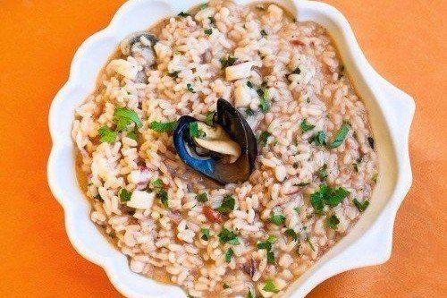 un piatto di risotto con fiori di mare su sfondo arancione