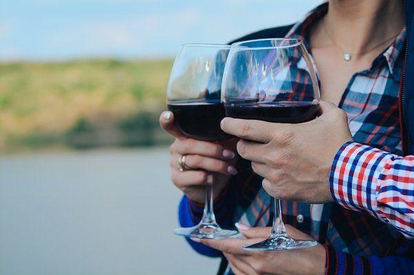 Facendo un brindisi con due bicchieri di vino rosso