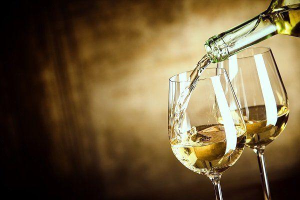 Riempiendo due bicchieri di vino bianco