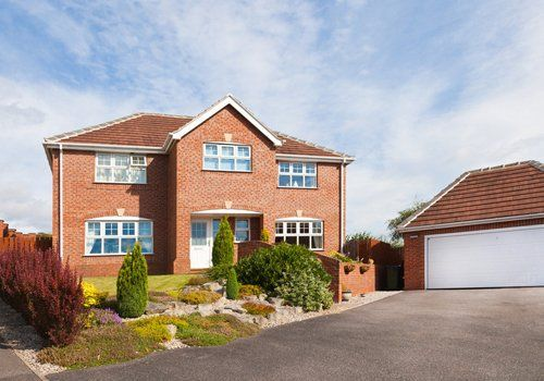 A large detatched property with a large garage and new tarmaced driveway