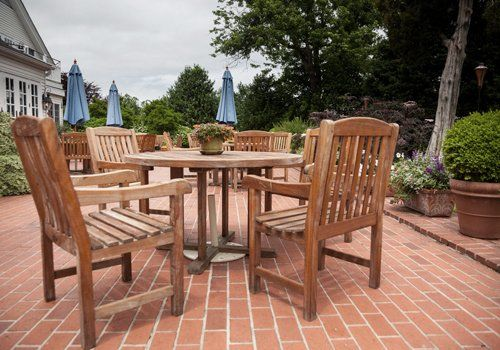 A large patio area made of red brick, with wooden garden furniture on it