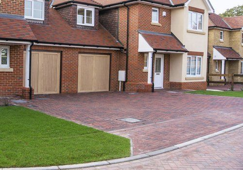A large property with a red brick driveway