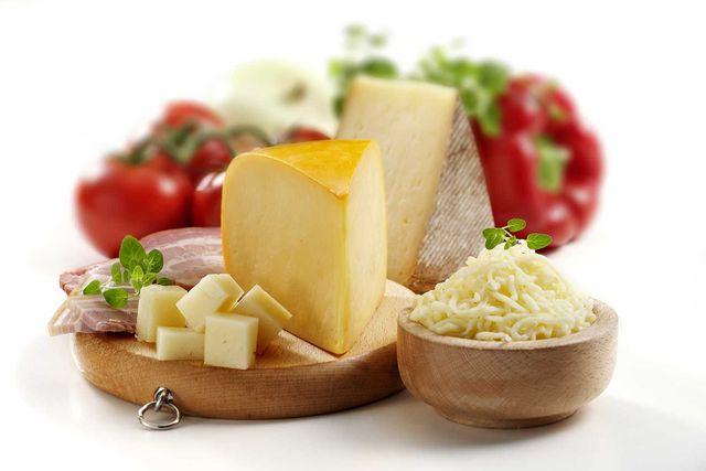 un tagliere con delle fette di formaggio accanto a della Verdura