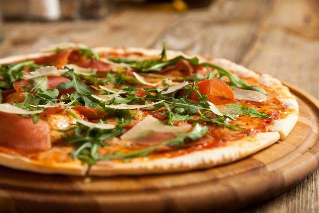 un tagliere con una pizza al prosciutto crudo e rucola