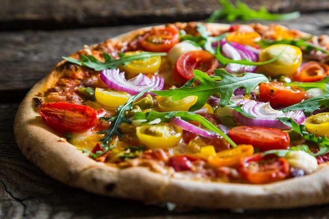 una pizza con pomodori gialli e rossi e della cipolla