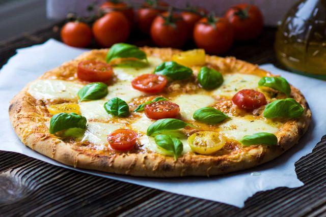 la pizza bianca con pomodori gialli e rossi a fette e basilico