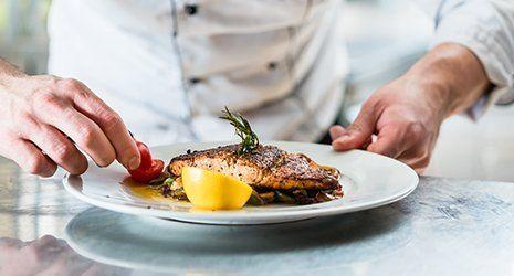 chef che guarnisce piatto di pesce