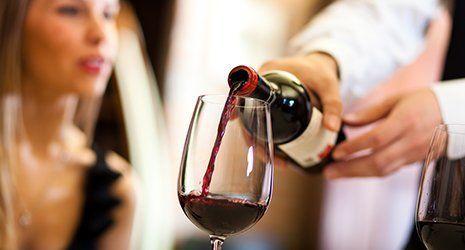 cameriere che versa del vino in un calice