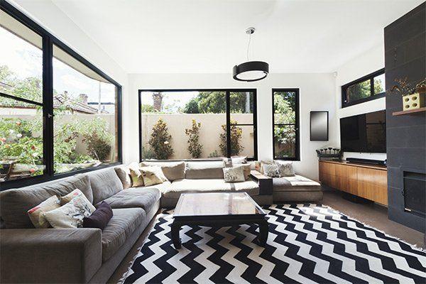 soggiorno con pavimento bianco e nero, divani e grandi finestre