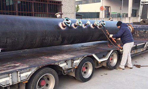 un uomo vicino a un grosso tubo sopra un rimorchio di un camion