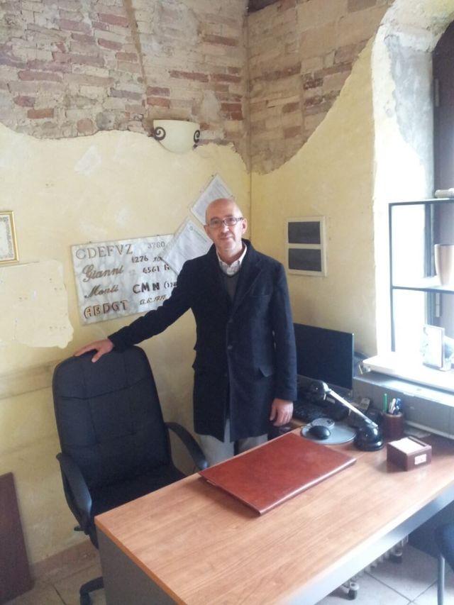 uomo con mano su sedia girevole nera vicino alla scrivania
