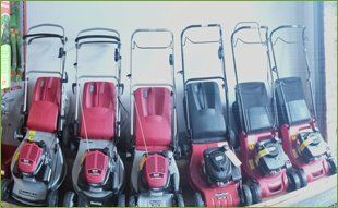 red and black lawnmowers lined up against a wall