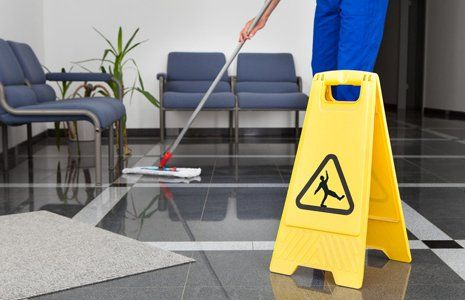 A man in blue overalls cleaning a tiled floor behind a yellow safety sign