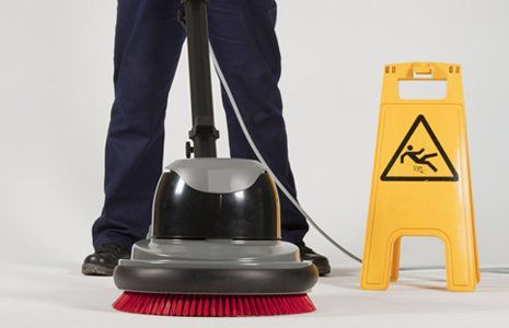 A man operating an industrial cleaner beside a yellow safety sign