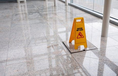 Yellow safety sign on a clean shiny marble floor