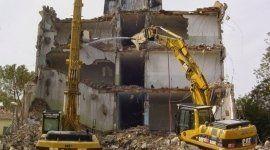 Due escavatori demolendo un edificio