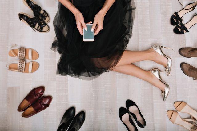 vista dall'alto di una donna con il cellulare e diversi tipi di scarpe per ogni occasione