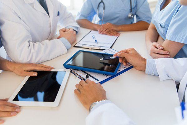 dei medici con camice bianco seduti al tavolo con i loro tablet  e dei rilievi di scrittura