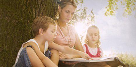 A nanny reading a story to kids