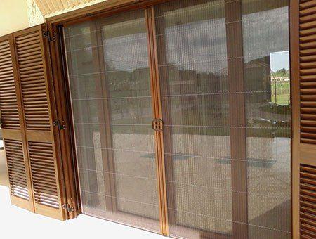 una porta finestra scorrevole e delle persiane in legno