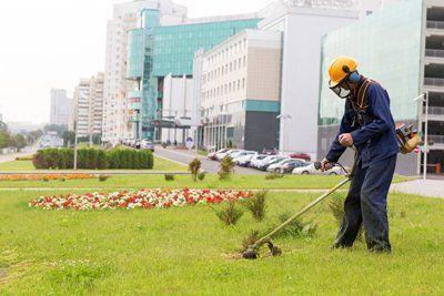 addetto con tuta da lavoro taglia l`erba di un giardino