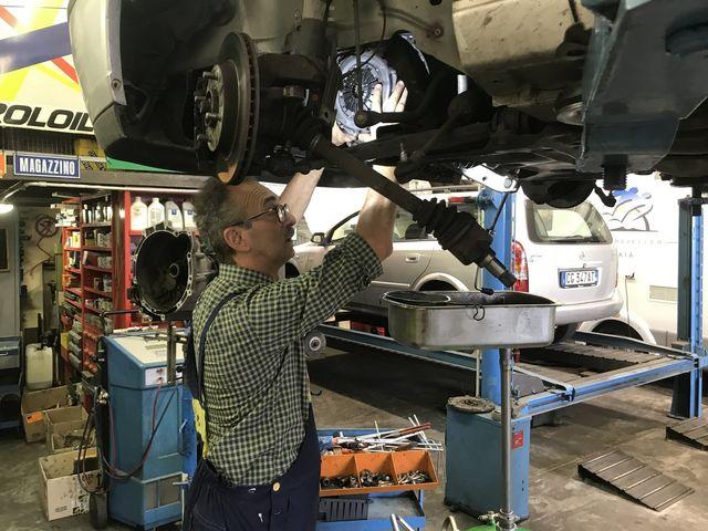 meccanico effettua riparazione su un'auto
